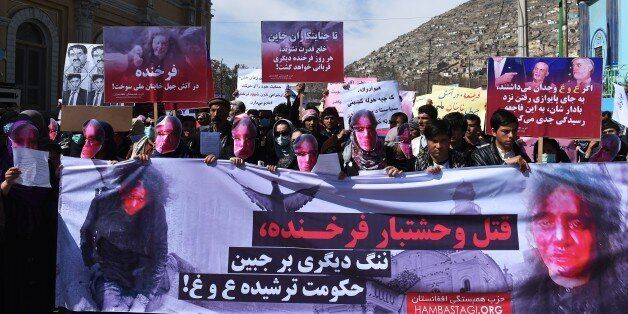 Afghan members of the Solidarity Party of Afghanistan wearing masks bearing an impression of the bloodied...
