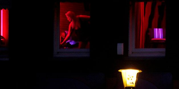 In this photo taken Monday Jan. 10, 2011 a prostitute advertises her wares behind red-lit windows in...