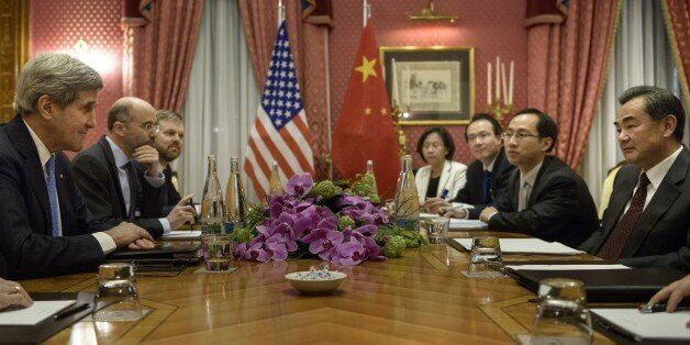 US Secretary of State John Kerry (L) and Chinese Foreign Minister Wang Yi (R) wait before the start of...