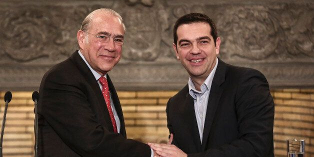 OECD Secretary General Jose Angel Gurria, left, shakes hands with Greek Prime Minister Alexis Tsipras...