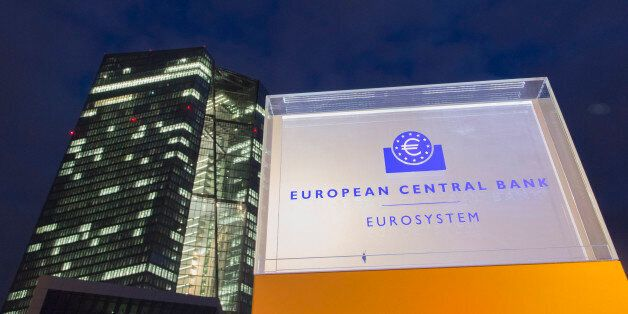 An illuminated sign for the European Central Bank (ECB) headquarters stands outside the main building...