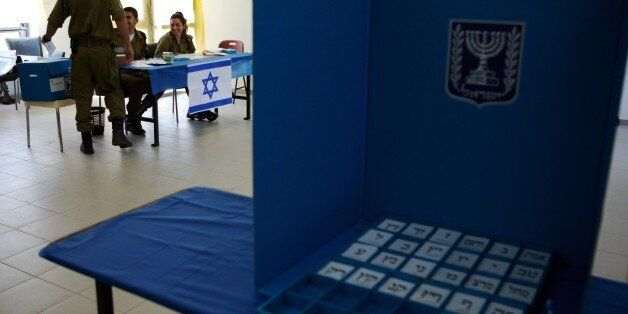 An Israeli soldier casts his vote at the Urim army base in the south of Israel near the border with the...