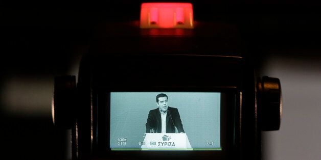 Greek Prime Minister and Syriza leader Alexis Tsipras is seen in a TV monitor as he delivers a speech...