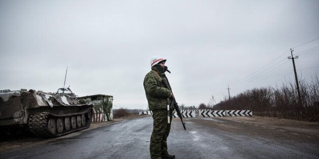 NOVOAZOVSK, UKRAINE - MARCH 04: A pro-Russian seperatist stands guard at a check point on the road heading...
