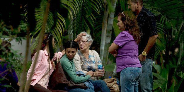 Josefa Alvarez de Gonzalez, center, is comforted by relatives of her husband, Rodolfo Gonzalez, outside...