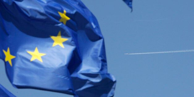 The flag of the European Union is caught in the wind as an unidentified aircraft flies over Brussels,...