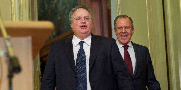 Greece's new Foreign Minister Nikos Kotzias, left, smiles as he arriving for a news conference after...