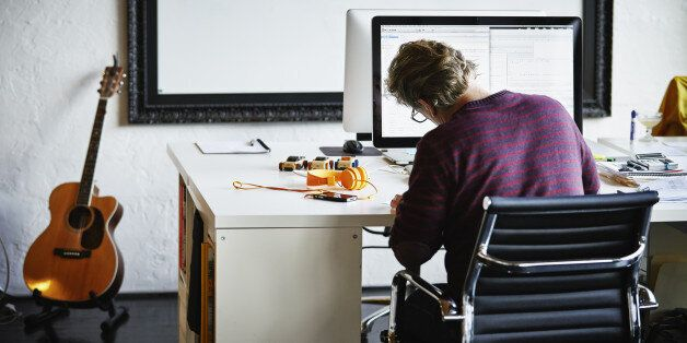 Businessman sitting at workstation in office writing on documents rear