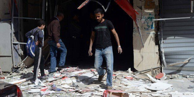 Egyptians inspect the damage outside offices of the Britain-based cell phone provider Vodafone after...