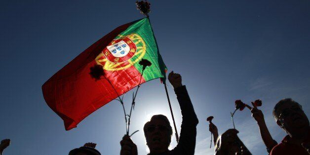 People holding red carnations and a Portuguese flag sing a protest song during a rally marking the international...