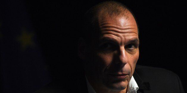 Greek Finance Minister Yanis Varoufakis holds a press conference, as an attendee turned of the lights,...