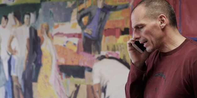 Greece's Finance Minister Yanis Varoufakis speaks on his phone at his office, in central Athens, on Saturday,...