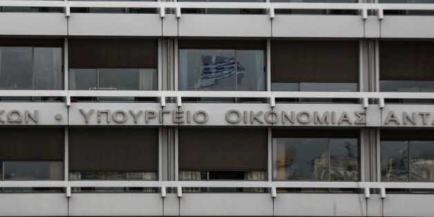 A Greek flag is reflected on a glass window of the Finance Ministry in Athens, Monday, Feb. 23, 2015....