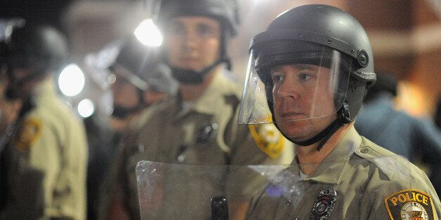 FERGUSON, MO - MARCH 11: A St. Louis County Police officer stands alert in riot gear during a protests...