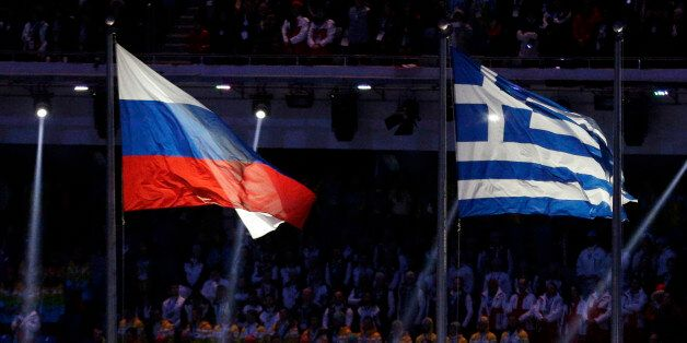Flagbearers carry the Olympic Flag, as the national flags of Russia, left, and Greece fly during the...