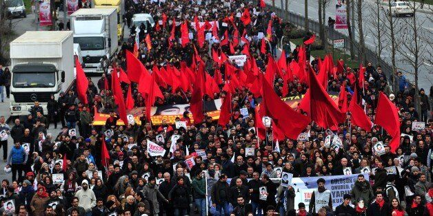 Demostrators march with red flags and posters of Berkin Elvan in Istanbul on March 7, 2015, as thousands...