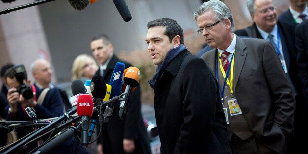 Greek Prime Minister Alexis Tsipras, center, speaks with the media as he arrives for an EU summit in...