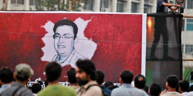 A Bangladeshi activist sets up a light on a poster displaying a portrait of Avijit Roy as others gather...