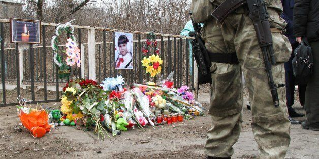 A Ukrainian soldier stands near the place where a Ukrainian armored vehicle ran over a family, killing...