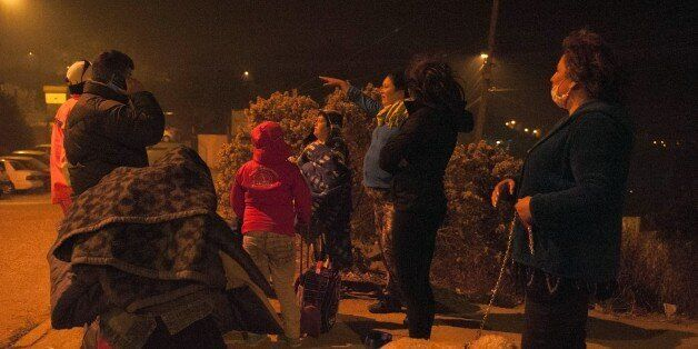 People are seen after being evacuated from their homes in Valparaiso, Chile, due to a forest fire that...