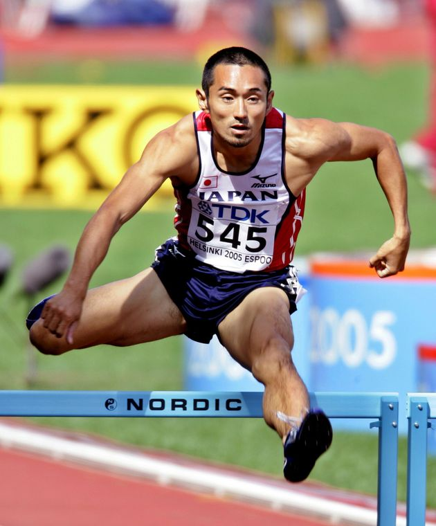 Dai Tamesue of Japan clears a hurdle in the fifth heat of the 400 metres men's hurdle event at the world...