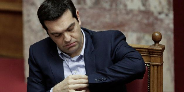 Greece's Prime Minister Alexis Tsipras looks at his watch during a parliament session in Athens, on Tuesday,...