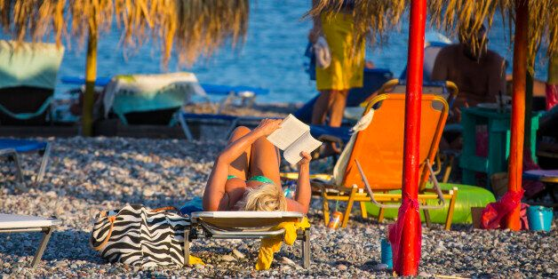 RHODES, GREECE - AUGUST 23: Woman in a bikini is reading and taking a sunbath at the beach in Gennadi...
