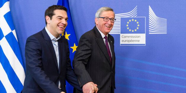 European Commission President Jean-Claude Juncker, right, walks hand in hand with Greece's Prime Minister...