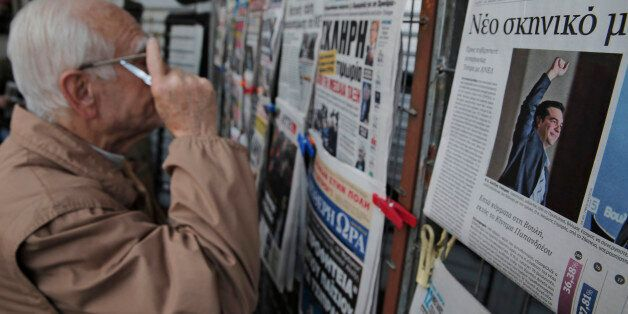 An Athenian reads newspapers featuring front page stories and photos of Alexis Tsipras, leader of Greece's...