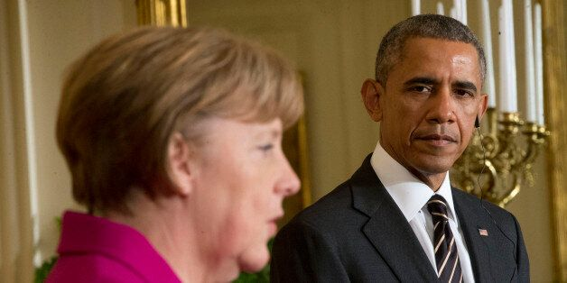 President Barack Obama listens as German Chancellor Angela Merkel speaks during their joint news conference...