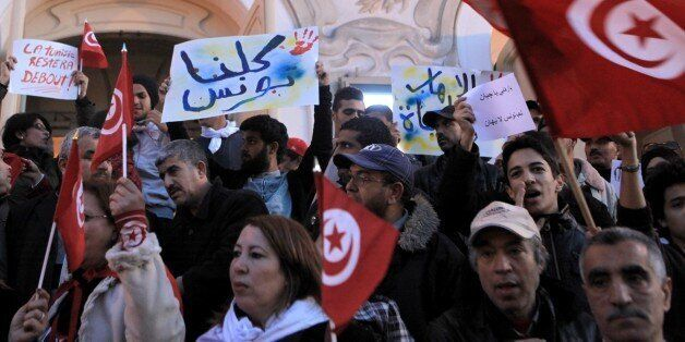 TUNIS, TUNISIA - MARCH 18: A group of people hold banners and shout slogans during a protest against...