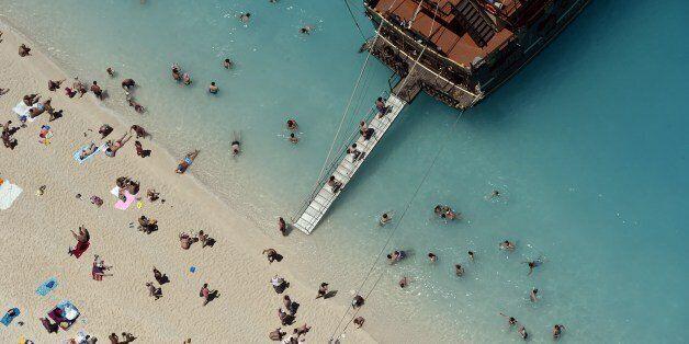 Tourists board a tourist boat as they enjoy the sunshine and the sea at a beach on Zakynthos island,...