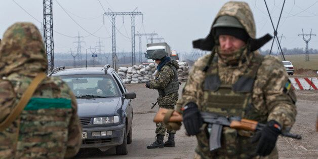 In this picture taken on March 3, 2015, a soldier checks a vehicle at an Ukrainian army checkpoint near...
