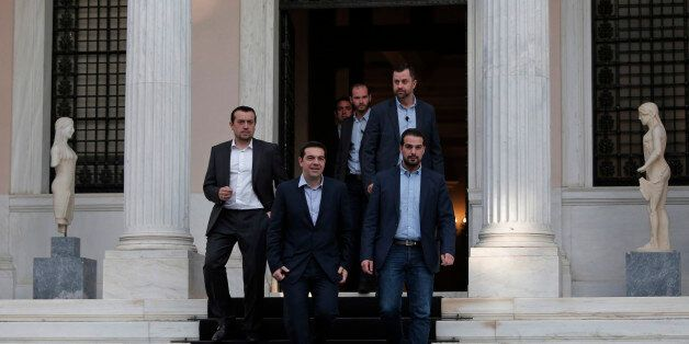 Greece's Prime Minister Alexis Tsipras, center, accompanied by close associates, walks out of his office...