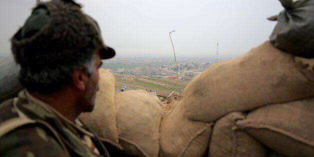 In this Thursday Jan. 29, 2015 photo, a Kurdish peshmerga fighter looks towards the city of Sinjar from...