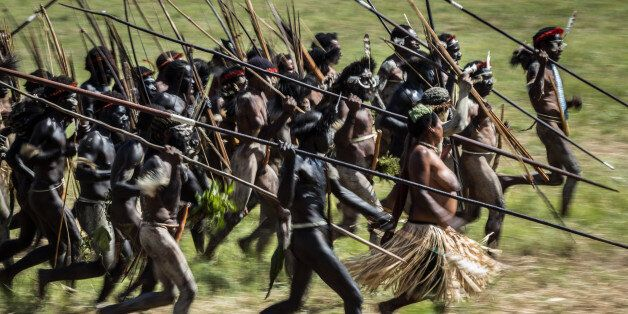 WAMENA, INDONESIA - AUGUST 08: The Papuanese tribes perform mock battles in an open field during the...