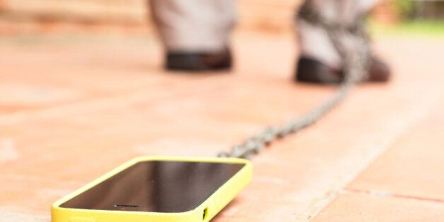 Man walking with smartphone chained to his leg. Conceptual picture for internet