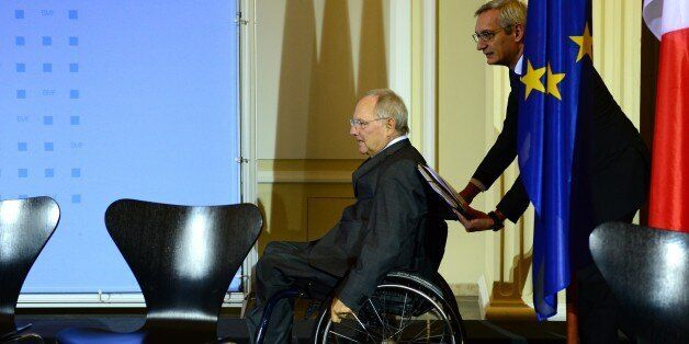 German Finance Minister Wolfgang Schaeuble (L) arrives on his wheelchair pushed by his spokesman Martin...