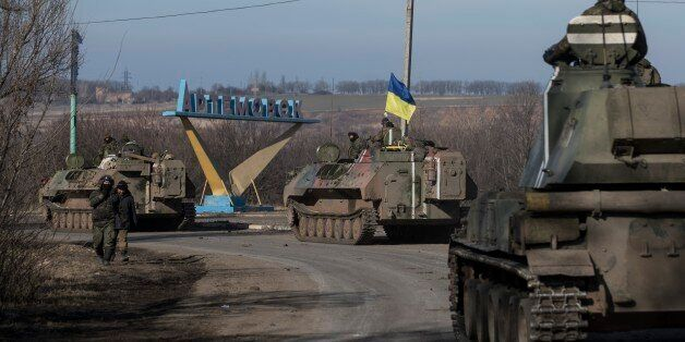 Ukrainian troops ride on armored vehicles towards Artemivsk, eastern Ukraine, Monday, Feb. 23, 2015....