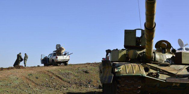 Syrian government forces gather on the Fatima hill overlooking the town of Kfar Shams, north of the southern...