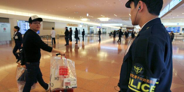 An officer from the anti-terrorism unit of Japan's Metropolitan Police Department keeps guard on the...