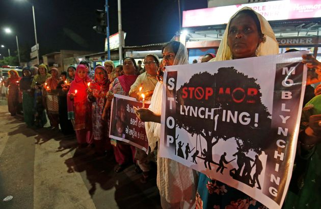 Women hold placards and candles during a protest against the mob lynchings across the country, in Ahmedabad,...
