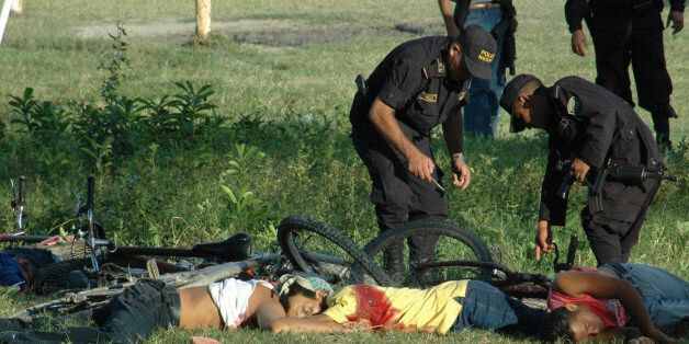 EDS. NOTE GRAPHIC CONTENT.- Police officers inspect the bodies of the victims of a massacre at a soccer...