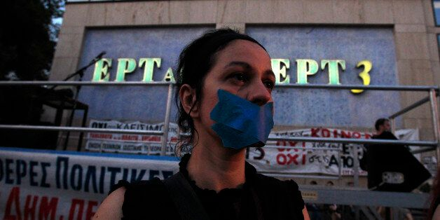 A protester with her mouth tapped takes part in a protest in solidarity to the employees of Greek state...