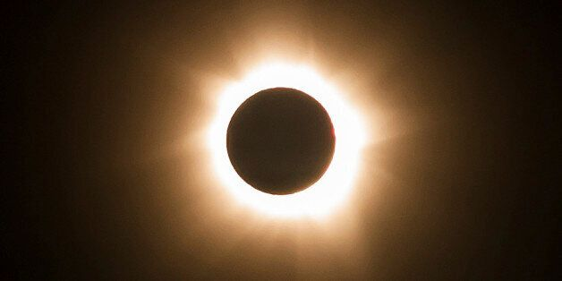 In this photo provided by Tourism Queensland, the moment of a total solar eclipse is observed at Cape...