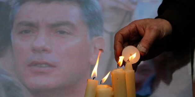 People light candles in memory of Boris Nemtsov, seen behind, at the monument of political prisoners...
