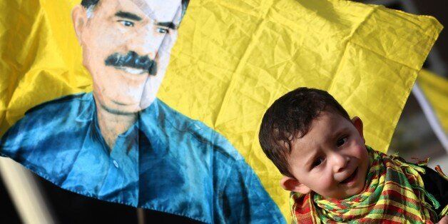 A child is seen in front of a flag bearing a portrait of the leader of the Kurdistan Workers Party (PKK)...