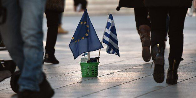 People walk next to a Greek and an EU flag in Athens on February 25, 2015. The hard work for Greece's...