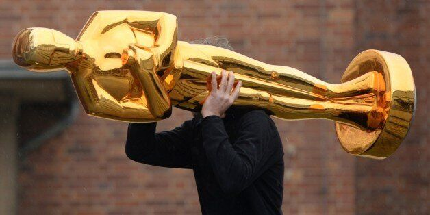 A worker carries an Oscar statue to a press event held by Filmstudios Babelsberg in Potsdam, eastern...