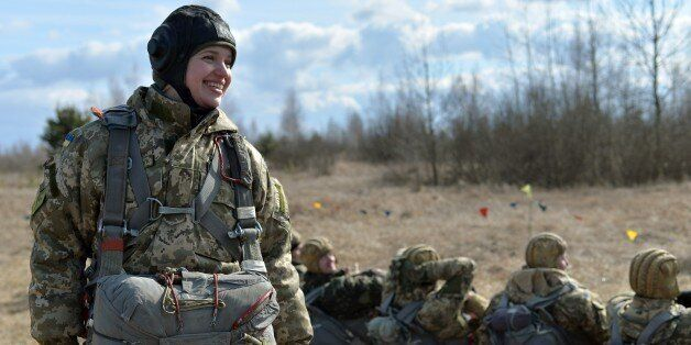 A Ukrainian paratrooper shares a laugh with comrades during military drills in the Zhytomyr region, some...